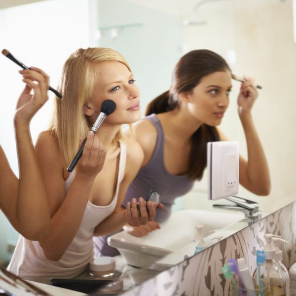 Shot of three friends applying makeup in front of the mirror